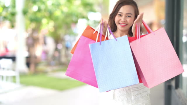 asiatiska mogna affärskvinna trevliga med shoppingkassar, blåser kyss, slowmotion - köpnarkoman bildbanksvideor och videomaterial från bakom kulisserna