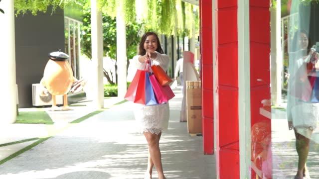 asiatiska mogna affärskvinna trevliga med shoppingkassar, slowmotion - köpnarkoman bildbanksvideor och videomaterial från bakom kulisserna