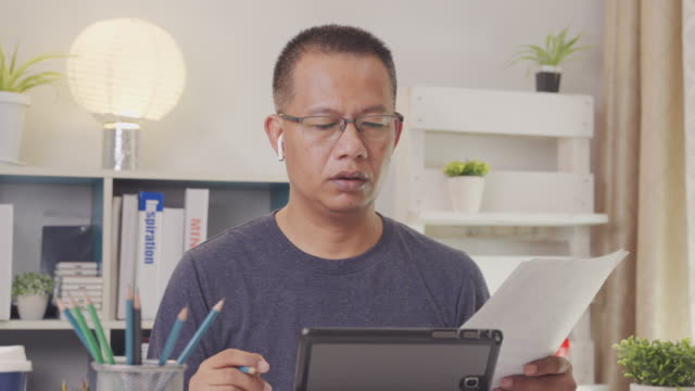 Asian men 40-50 years old in casual attire are meeting online with staff via video conferencing system. While he was working at home due to the coronavirus.