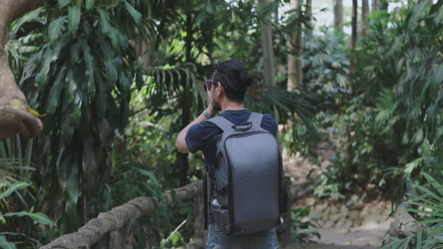Asian men backpacks and traveler walking together and happy are taking photo on forest  ,Relax time on holiday concept travel video