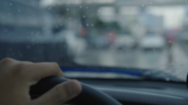 Asian men drive during heavy rain during the day.