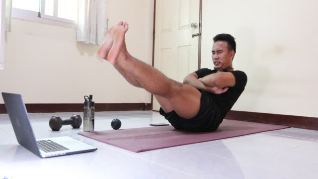 Asian men exercising and working out at home, He is watching youtube videos and learning the exercises. video