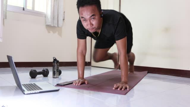 Asian men exercising and working out at home, He is watching youtube videos and learning the exercises. Asian men exercising and working out at home, He is watching youtube videos and learning the exercises. bodyweight training stock videos & royalty-free footage