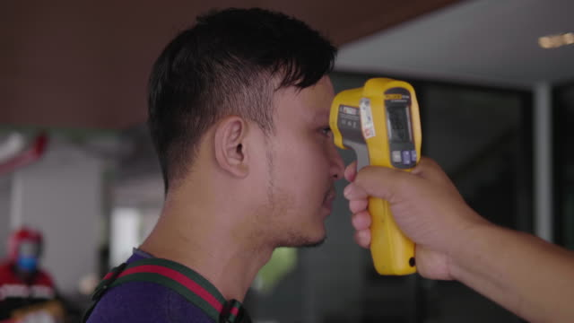 Asian men measure fever using a checker