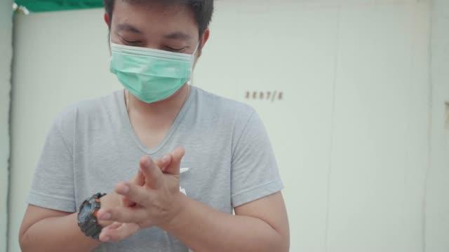 asiatische männer tragen maske gesicht waschen hände mit gel, schützen virus covid-19. - krankheitsverhinderung stock-videos und b-roll-filmmaterial