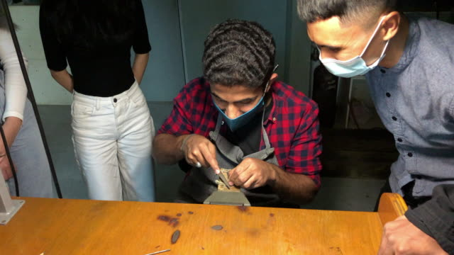 Asian middle eastern students showing his jewelry to teacher in college workbench