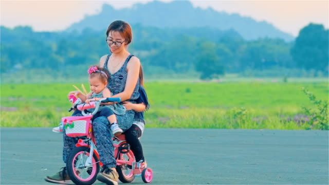 Asian Mom And Daughter Cycling Together video