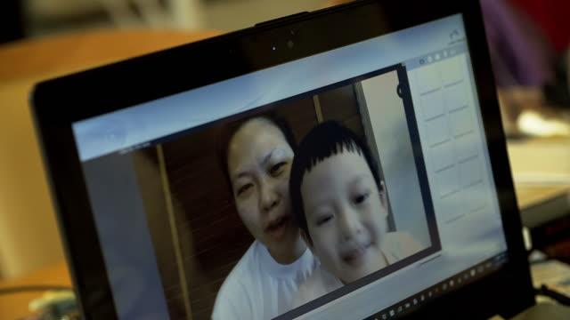 4K: Asian mom and son on video call facetime chatting via laptop computer video