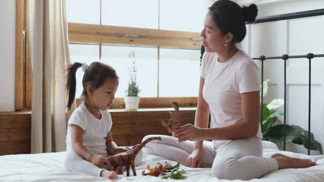 asian mom with kid daughter playing toys sit in bed - two students together asian video stock e b–roll