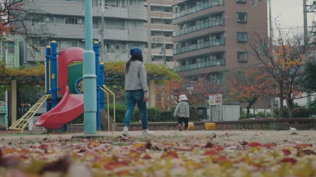 亞洲母親和嬰兒在秋季公園玩耍 - 休閒器具 個影片檔及 b 捲影像