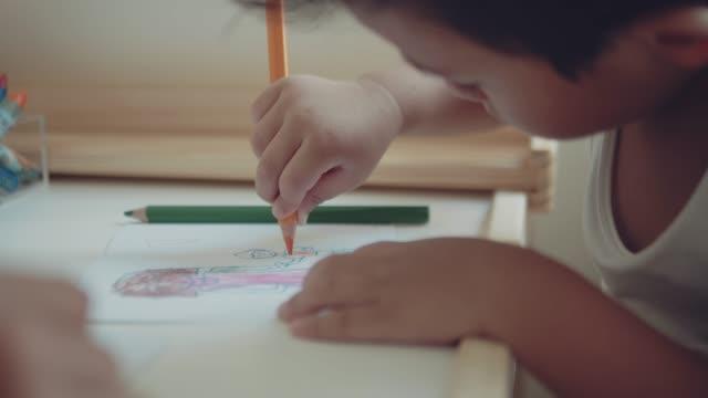 子供たちが自宅の部屋でテーブルの上に母の日のためのグリーティングカードを作るアジアの母子。バンコク。 - スケッチ点の映像素材/bロール