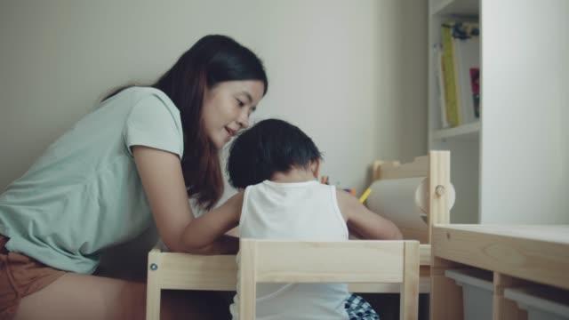 madre e figlio asiatici che fanno il biglietto d'auguri per la festa della mamma sul tavolo in camera a casa. bangkok, thailandia. - matita colorata video stock e b–roll