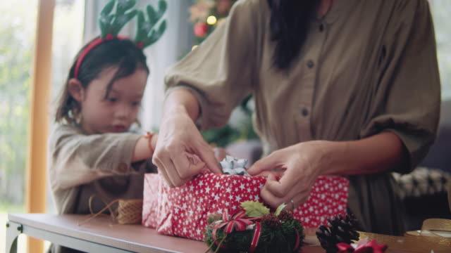 l'assistenza della madre e del bambino asiatica che confeziona i regali di natale. - avvolto video stock e b–roll