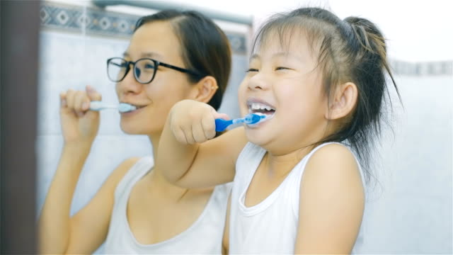Asian Mother and daughter brushing teeth in bathroom together video