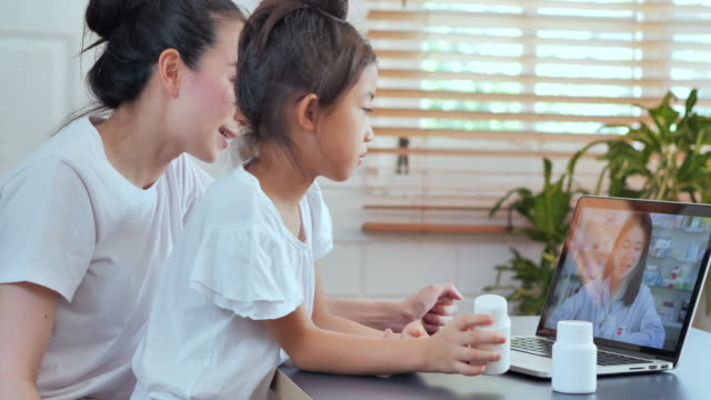 Asian mother and daughter looking at pill bottle and listening to asian women pharmacist explaining medicine in consultation medicine to video conference at home.Family, Video call, Children, Technology, Medical, Care, Education, Medicine and healthcare - vídeo