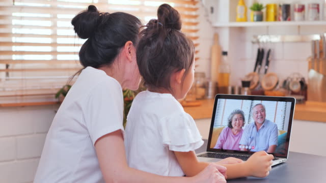 Asian mother and daughter on video conference for video call at home with grandparent family abroad,during social distancing using laptop computer and video conferencing technology.Social teleconferencing video