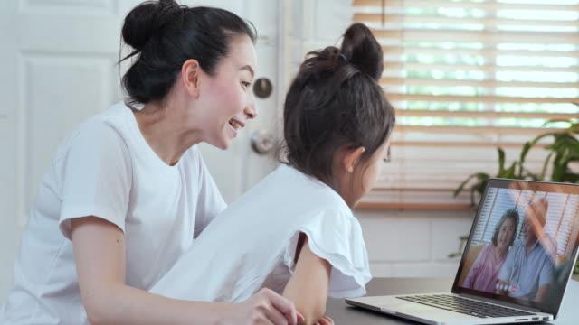 アジアの母と娘は、ラップトップコンピュータとビデオ会議技術を使用して社会的な混乱の間に、海外の祖父母の家族と自宅でビデオ通話のためのビデオ会議に。ソーシャルテレビ会議 - 人里離れた点の映像素材/bロール