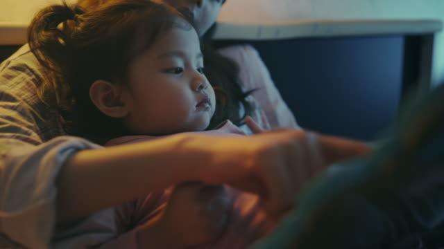 vídeos de stock e filmes b-roll de asian mother and daughter reading book and pointing to a book at home in the bedroom. bedtime story - baby super hero