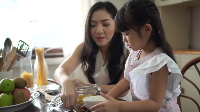 asian mother and daughter sit and cook together on the kitchen table at home