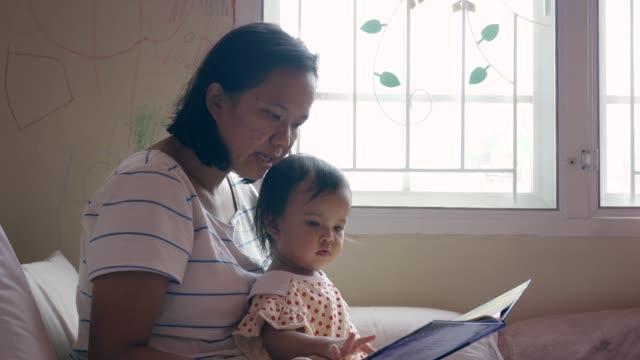 アジアの母親と彼女の娘は、窓からの日光で昼間に本を読む - 画像や映像点の映像素材/bロール