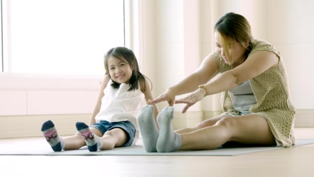 vídeos de stock e filmes b-roll de asian mother and her kid daughter doing stretching exercise at home - training