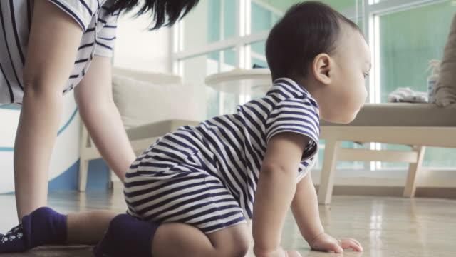vidéos et rushes de une mère asiatique et petit bébé à ramper sur le sol dans le room.4k de vie - ramper