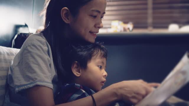 stockvideo's en b-roll-footage met aziatische moeder en kleine zoon lezen in bed 's nachts. - comfortabel