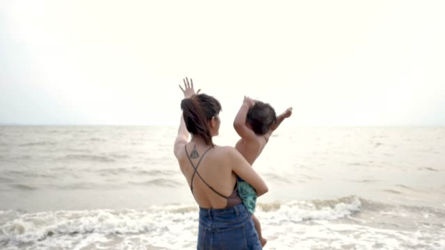 Asian mother and son on the beach Asian young mother holding baby and walking on beach. Pattaya Beach, Thailand. tattoo stock videos & royalty-free footage