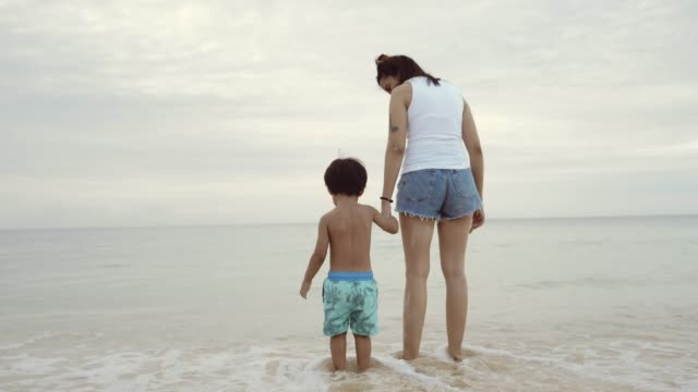 Asian Mother and Son Playing at the Beach Young Mother And Son Holding Hands And Walking On The Beach life balance stock videos & royalty-free footage