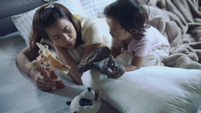 Asian mother and son playing toys