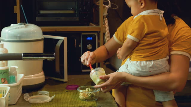 Asian Mother And Son Preparing Baby Food