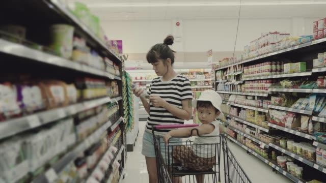asiatische mutter und sohn in einem supermarkt einkaufen - supermarkt einkäufe stock-videos und b-roll-filmmaterial
