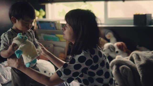 彼女の男の子のベッドの上に服を変更するアジアの母 ビデオ