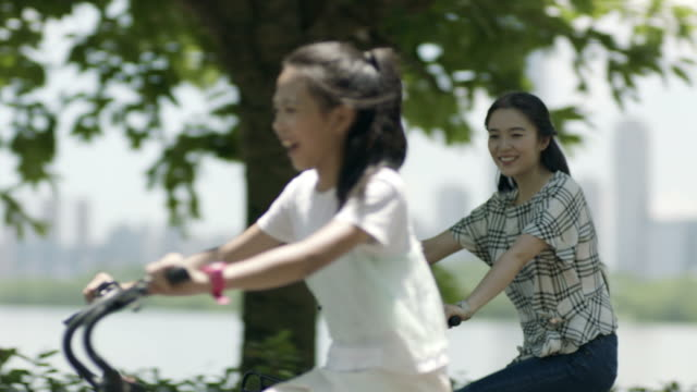 asian mother & daughter cycling on lakeside promenade in summer