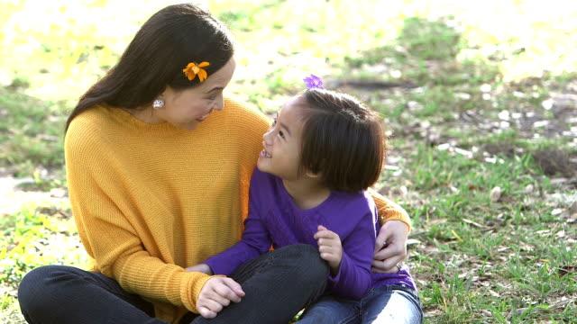 asiatiska mor, dotter i park talar, blomma i håret - enbarnsfamilj bildbanksvideor och videomaterial från bakom kulisserna