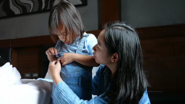 Asian mother dressed for daughter to prepare to go to school in the morning.
