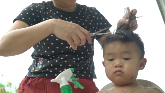 vidéos et rushes de mère asiatique donnant la coupe de cheveux de son fils à la maison pendant la quarantaine. - coiffure