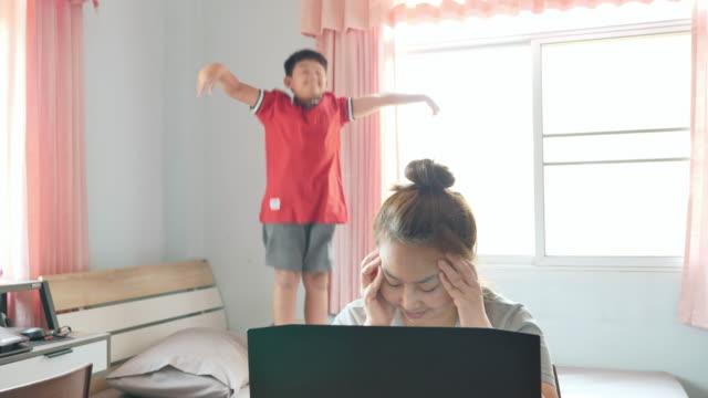 亞洲母親頭痛在家用筆記型電腦工作,兒子發出噪音,跳到床上打擾上班的婦女早上陽光從窗戶發出。 - 三四十歲的人 個影片檔及 b 捲影像