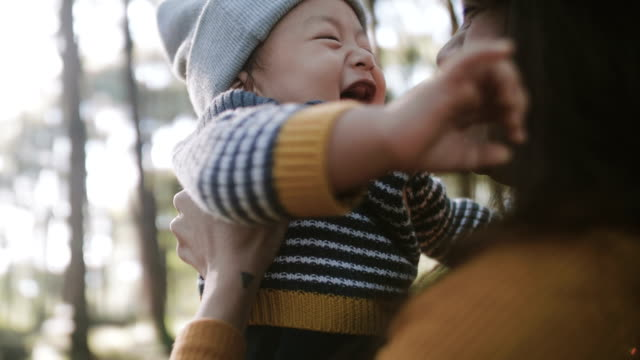 vídeos de stock e filmes b-roll de asian mother holding and kissing her baby boy - together