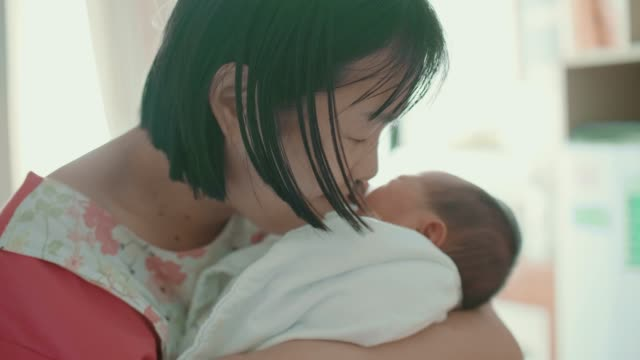 Asian Mother Holding Newborn in Her Arms and Kissing