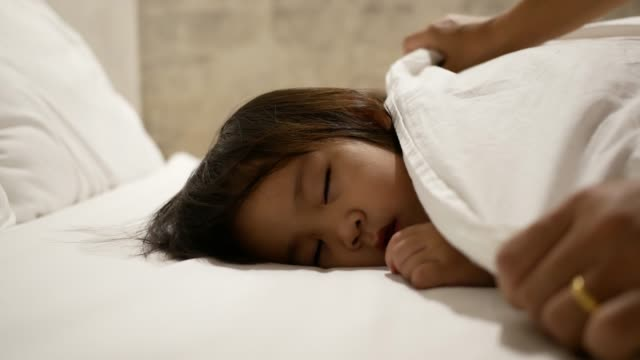 Asian mother is putting blanket on her daughter who is sleeping in the bed and goodnight kiss with love. Health care concept. video