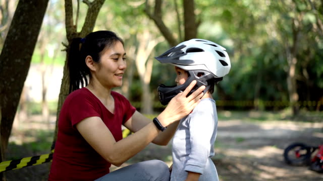 SLO MO Asian Mother is putting safety helmet on his little son's head.
