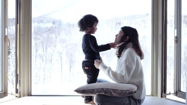 asiatiska mamma kysser och ser snö fönster söta små pojkar hemma. - hokkaido bildbanksvideor och videomaterial från bakom kulisserna