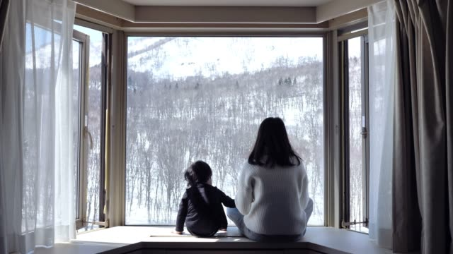 vídeos de stock e filmes b-roll de asian mother kissing and looking snow window cute little boys at home. - family christmas
