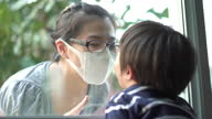 istock Asian mother looking through the window to her son at home in Coronavirus situation 1305358462