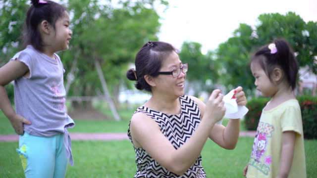 Asian mother puts on her child on a protective face mask at public park