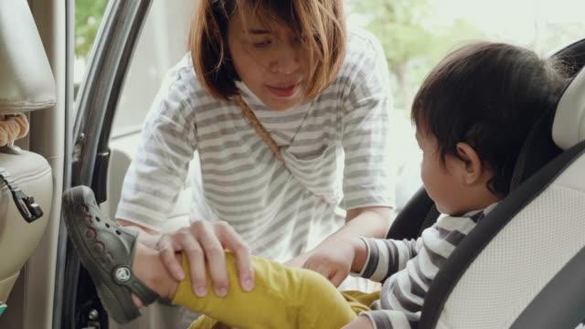 vídeos y material grabado en eventos de stock de asia madre poner a hijo de bebé en asiento - protección