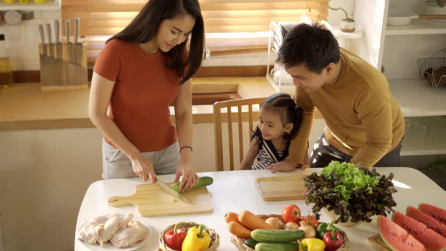 Asian  Mother teaching family how to cooking in kitchen
