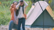 istock Asian mother teaching little girl about sustainability in the forest and excited little girl on a camping trip with binoculars looking for adventures in nature green forest.Teaching Children about Sustainability 1211303701