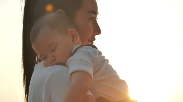 Asian mother with baby son sleeping and walking with fun along edge of sunset sea surf on sand beach.Happy family holidays.Family,Lifestyle,People,Life insurance,South East and East Asia: Asian Babies,Vacations video